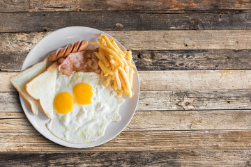 Top view of american breakfast with scrambled eggs,bacon,toast,french fries and sausage on wooden table background.
