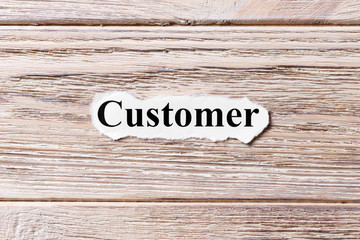 Customer of the word on paper. concept. Words of Customer on a wooden background