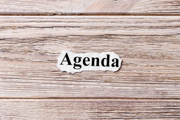 AGENDA of the word on paper. concept. Words of AGENDA on a wooden background