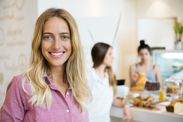 Young woman smiling cheerfully in small business, portrait