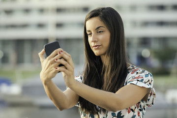 Woman taking selfie using smart phone