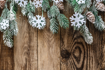 spruce branches with snow on wooden background