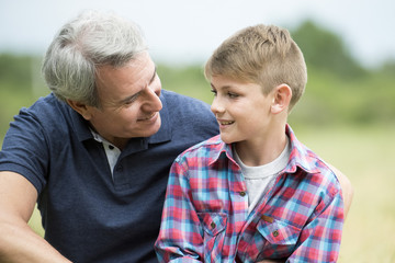 Grandfather and grandson outdoors, portrait