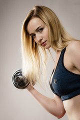 Fit woman doing exercise with dumbbells