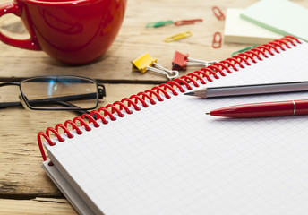notebook on the spring and pens,  wooden table top, desk