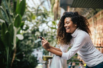 Adorable dark skinned woman with afro hairstyle using her phone.