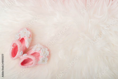close up baby girl knitted shoes on white blanket backgroundhappy new year greeting card