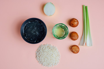 Ingredients of risotto organized on pink pastel surface