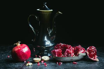 Black teapot and pomegranates