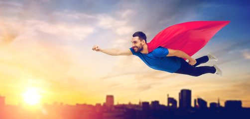 happy man in red superhero cape flying over city