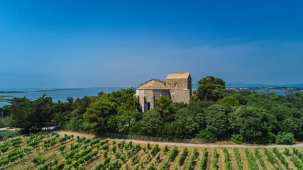 Aerial top view of old church on island from above, canal du Rhone a Sete, Camargue, France