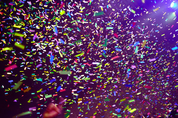 Confetti fired on air during a concert. People are happy and with hands in the air. Image ideal for backgrounds. Multicolor are the confetti in the picture