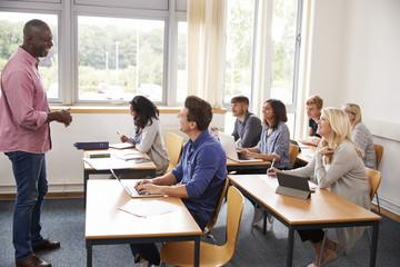 Male Tutor Teaching Class Of Mature Students