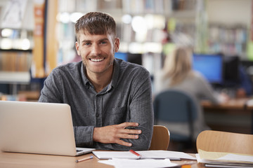 Portrait Of Mature Male Student Using Laptop In Library