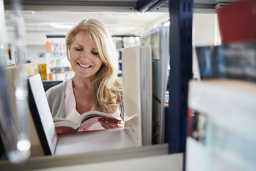 Mature Female Student Browsing Through Books In Library