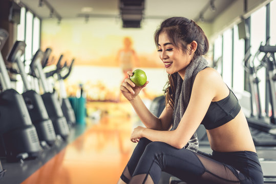 Asian woman holding and looking green apple to eat with sports equipment and treadmill in background. Clean food and Healthy concept. Fitness workout and running theme.