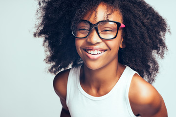 Laughing African girl in glasses standing against a gray backgro