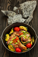 Pork cutlet on a bone with baked vegetables.