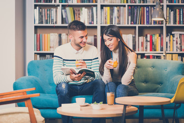 Beautiful young happy romantic couple in bookstore caffe or coffee bar. Young people in library