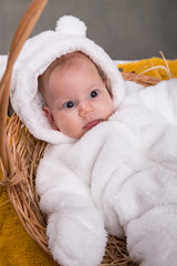 little baby in white bear costume on yellow blanket