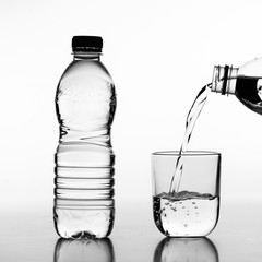 Hand holding drinking water bottle pouring water into glass on black and white background