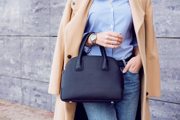 Wall Mural - Trendy woman in beige coat and jeans with black big bag