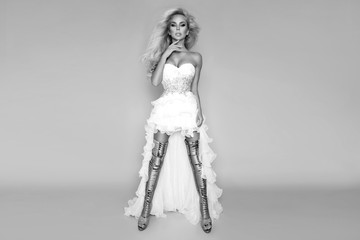 Beautiful blonde bride in a wedding dress and amazing gold shoes