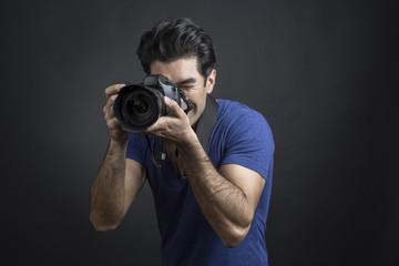 Fotografo con capelli neri e maglietta blu tiene una macchina fotografica reflex in mano mentre è intento a scattare una fotografia - sfondo scuro