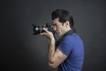 Fotografo con capelli neri, reflex in mano e maglietta blu è intento a scattare una fotografia - sfondo scuro