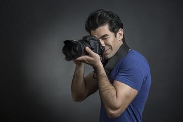Fotografo con capelli neri e maglietta blu è intento a scattare una fotografia - sfondo scuro