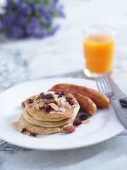 Breakfast Pancake and Sausage Top with Almond and Raisin on white plate