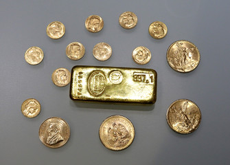 A gold ingot and gold coins are seen in this illustration picture
