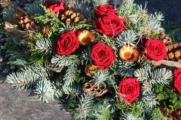 Autumn arrangement with roses in a cemetery, herbstliches Blumengesteck mit roten Rosen auf einem Grab zu Allerheiligen