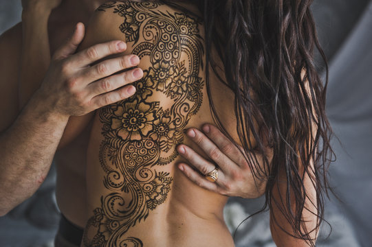 A beautiful pattern made with henna on the bare back of the girl 220.