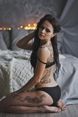 Portrait of a beautiful girl in her underwear sitting on the floor by the bed