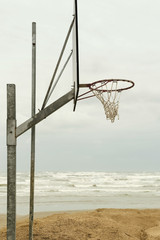 Old basketball hoop in a winter beach, sea on the background