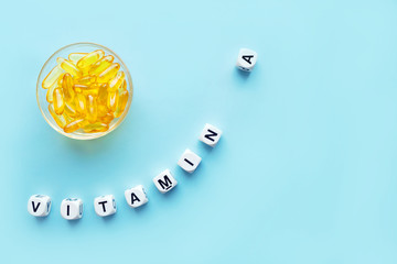 Yellow capsules in the round glass bowl and the word vitamin A from white cubes with letters on a blue background. healthy and medical concept. retinol, retinal, retinoic acid,  provitamin A