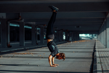 Young man doing hand stand in the urban environment