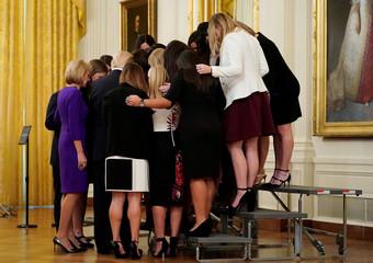 U.S. President Donald Trump prays with the Oklahoma Women's Softball team as he greets members of Championship NCAA teams in Washington