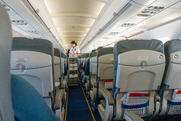 Steward offers food and drinks to economy class passengers on the plane