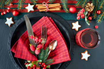 Black plates and vintage cutlery with Christmas decorations in green and red