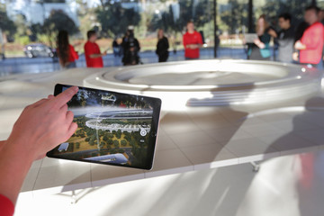 An Apple employee uses an iPad with an augmented reality app on it to show off features of the new Apple Park at the Apple Visitor Center in Cupertino