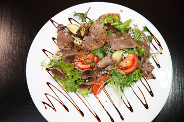 Salad with beef tongue with vegetables and herbs, dressed with sauce on a white plate.