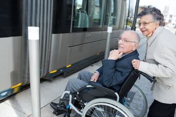 Elderly woman pushing wheelchair bound husband onto tram
