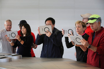 Visitors use iPads with augmented reality apps on them to discover features of the new Apple Park at the Apple Visitor Center in Cupertino