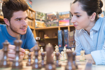 young couple sitting at a shop playing chess