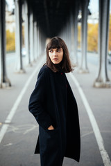 Female beauty concept. Portrait of fashionable young girl in casual black jacket posing on the street.