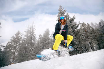 girl snowboarder in jump at ski resort in the mountain