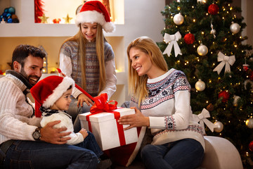 Boy receiving Christmas gift in big box from parents