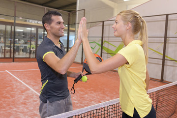 male and female tennis players shaking hands over the net